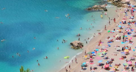 Aerial top view of Mediterranean sea beach full of tourists people and umbrellas during summer vacation travel, drone fly bird high above beautiful blue water, French Riviera, south France, Europe, 4K