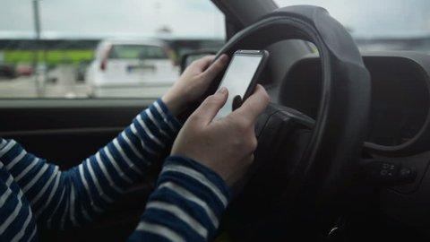 Woman using mobile smart phone while driving car, dangerous behavior in traffic