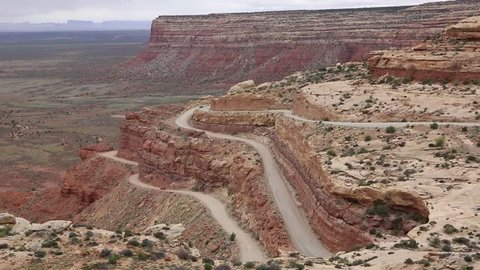 Red car driving down Moki Dugway - Utah
