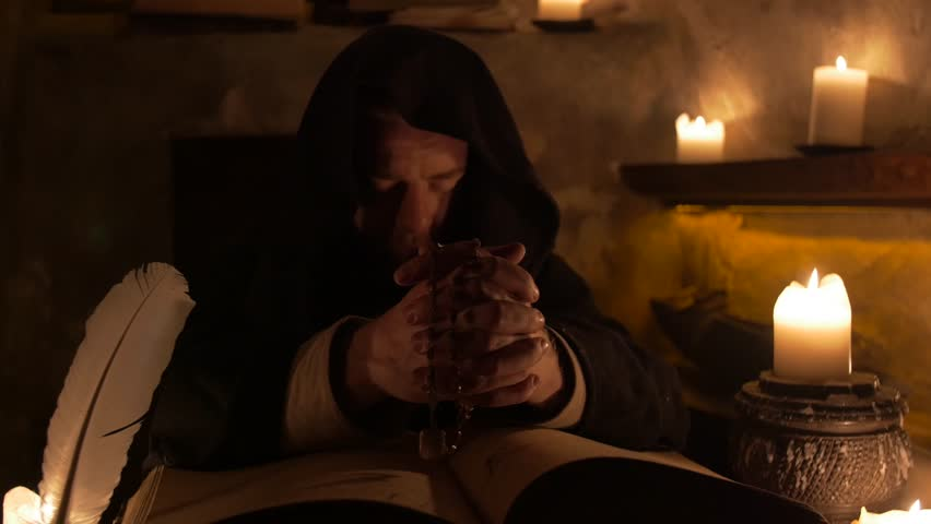 Mysterious medieval monk praying in the walls of the castle in 4K UHD video.