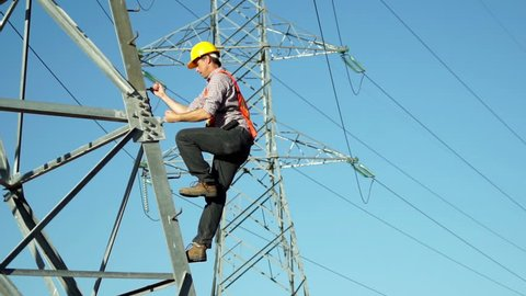 Technician in a safety vest and hard hat climbs high tension electrical tower which is part of the infrastructure for electricity distribution.