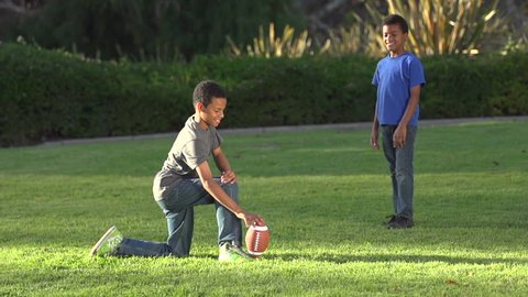 Big brother playing a trick on little brother as he tries to kick a football. - Model Released - 1920x1080 - Full HD