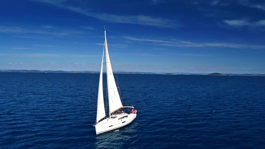 Yacht sailing on open sea at sunny day. Yachting. Yacht video. Yacht drone video. Sailing video. Sailing boat. Sailing aerial video. Sailing yacht.