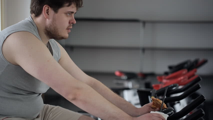 Tired man with an angry expression on his face eating pizza, engaging on an exercise bike