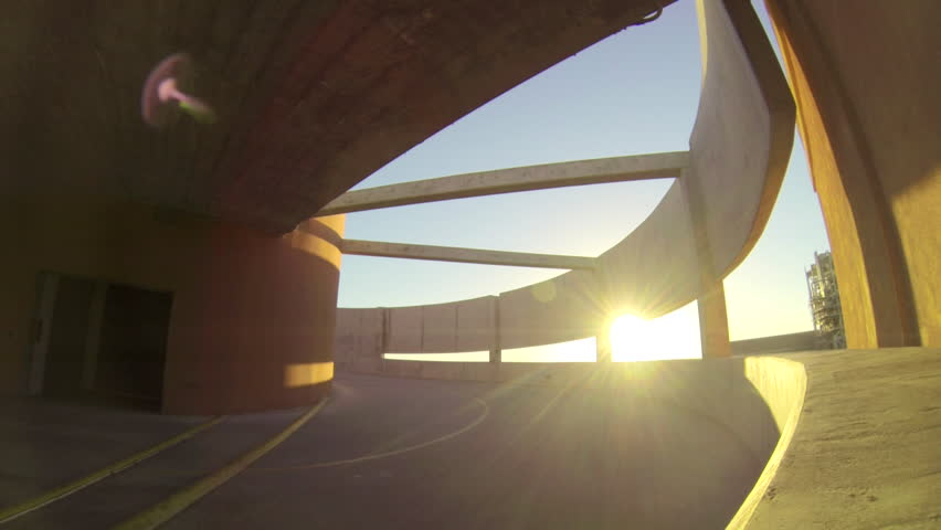 Silhouette of a young man skateboarding down a spiral ramp in a parking garage at sunset. - Model Released - 1920x1080 - Full HD - filmed at 59.94 fps | Shutterstock HD Video #16643566