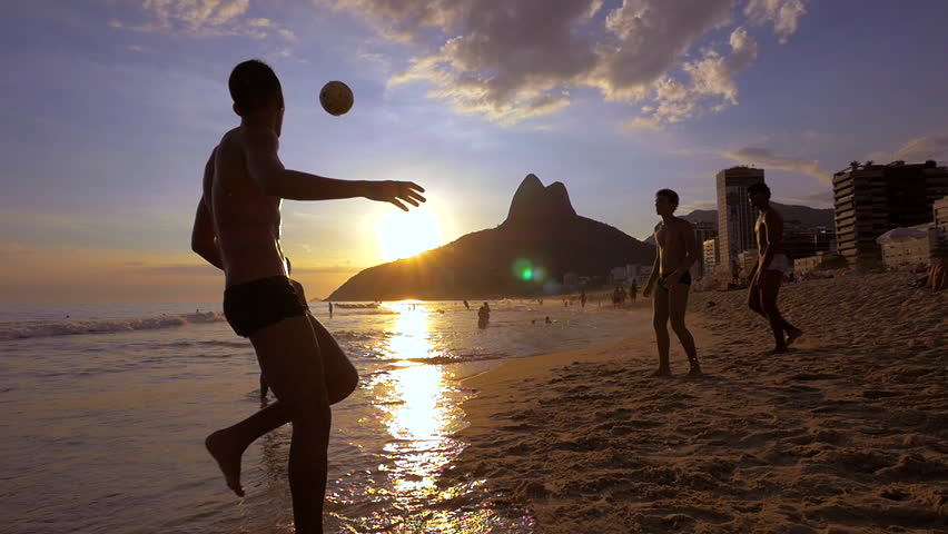 Rio de Janeiro, Brazil - Circa February, 2016: Slow motion shot of locals playing ball at sunset at famous Ipanema beach in Rio de Janeiro, Brazil. #16660396