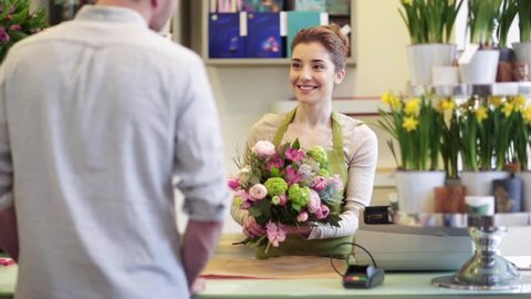 people, shopping, sale, floristry and consumerism concept - happy florist woman wrapping flowers in paper and giving them to man at flower shop