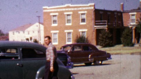 ANCHORAGE, ALASKA - 1955: Man making funny face about to enter classic car parked.
