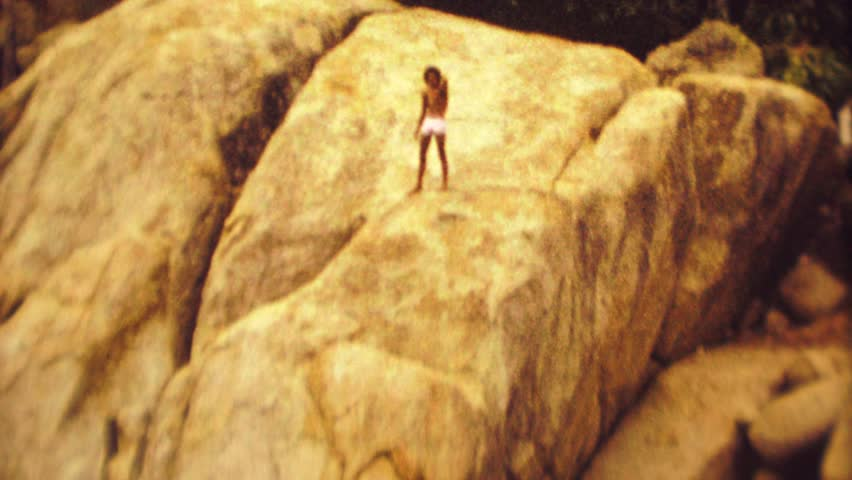ACAPULCO, MEXICO 1974: Native cliff diver jumps high rock into deep ocean waters.