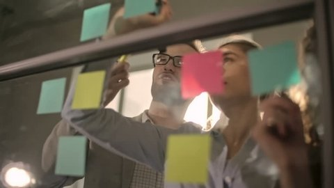 Young business team brainstorming and writing down ideas on sticky notes attached to glass wall, shot on Sony NEX 700
