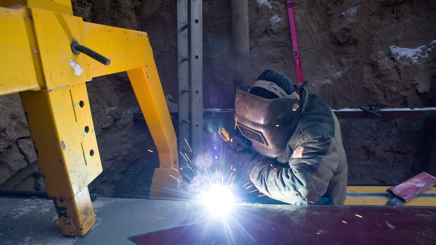 Builder welds parts outdoors. Installation of piping under ground in the winter day. Man work in gloves and protective clothing in the pit. Dangerous manual labor outside. Merge structure of details