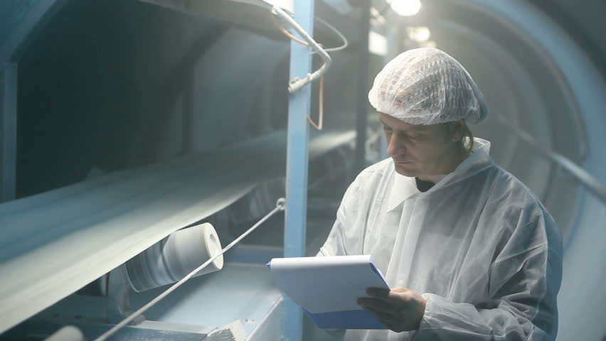 Quality inspector monitoring the process of crystal sugar production.  Sugar Refinery. Industrial Worker. White Sugar.  Production Line.