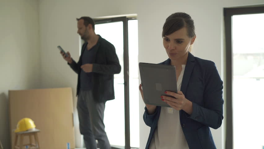 Woman with tablet looking around her new home, male architect checking apartment  | Shutterstock HD Video #16807633