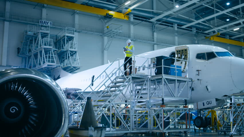 Engineer in Safety Vest Standing next to Airplane in Hangar. Shot on RED Cinema Camera in 4K (UHD).