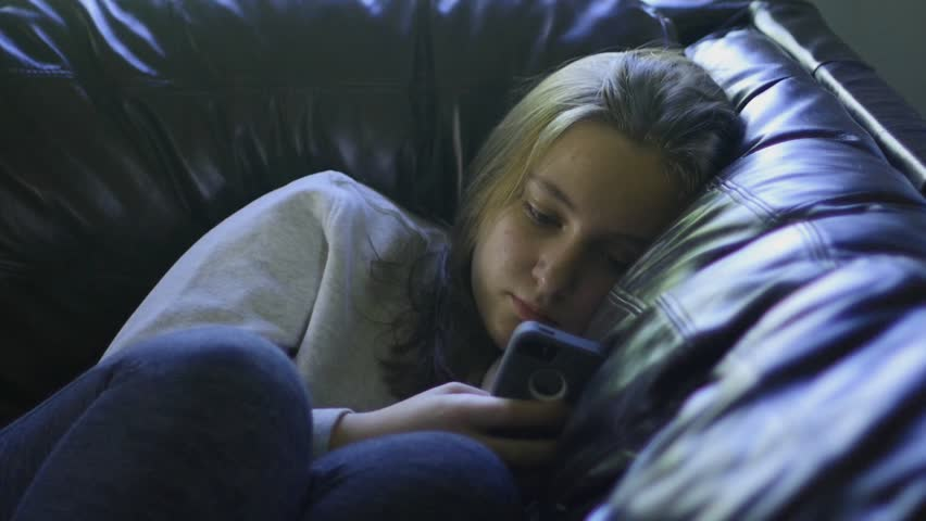 A bored teenage girl sending a text message on her cell phone
