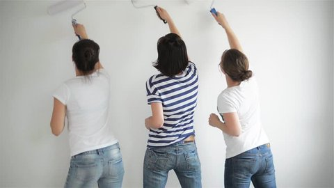 Friends makes repairs at home. Funny girls dance and paint the walls in the flat, good mood, making repairs and dance