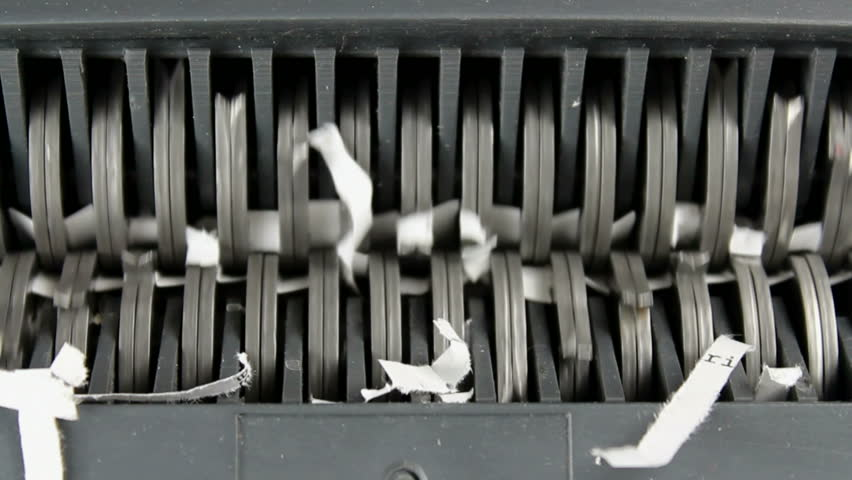 Close-up of a document cut into strips by the sharp blades of a paper shredder. 1080p