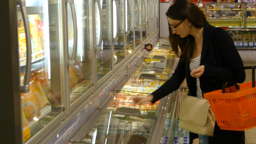 KHARKIV, UKRAINE - MAY 21, 2016: Young woman buying dairy or refrigerated groceries at the supermarket in the refrigerated section opening glass door of the fridge