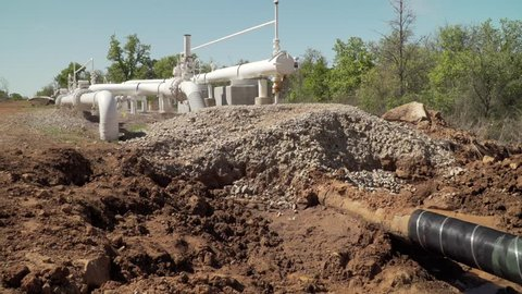 Camera pans to the right starting with the above ground oil pipeline equipment then to the exposed underground pipeline exposed in the trench.