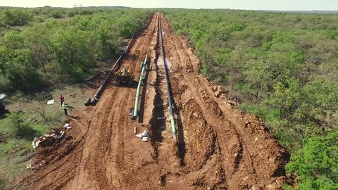 Fly over of showing a large oil pipeline exposed that is under construction.