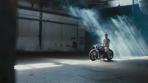 4K cinemagraph - young Caucasian male biker in shorts sitting on his custom cafe racer motorcycle in large warehouse garage looking forward. Background fog seamless loop