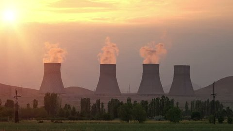 Sunset rays over cooling towers of nuclear power plant emitting steam
