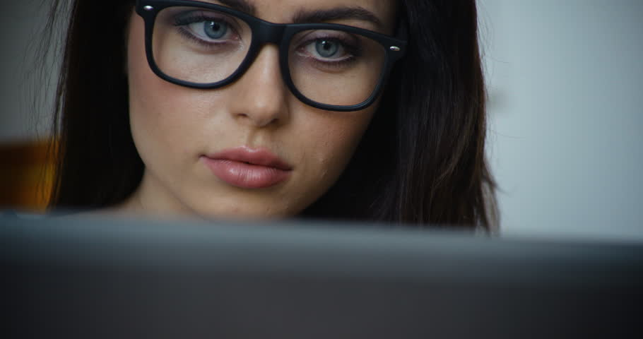 Beautiful brunette woman with brown hair and glasses using a laptop computer, close-up | Shutterstock HD Video #16927159