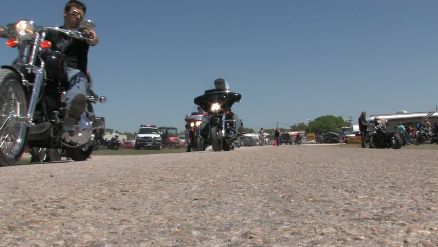 Motorcycles at a rally in south Texas. Low angle with bikes and riders passing as they ride forwards from the entrance gate.