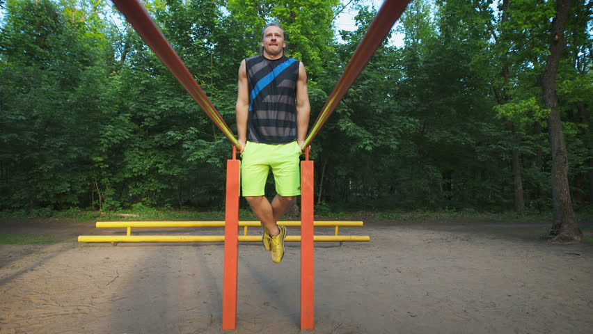 Muscular man during his workout in park. Dips, exercise chest and triceps. | Shutterstock HD Video #16951426