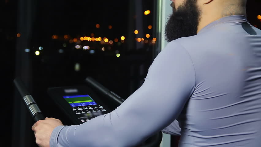 Bearded man looking at night cityscape through window after workout in gym #16956946