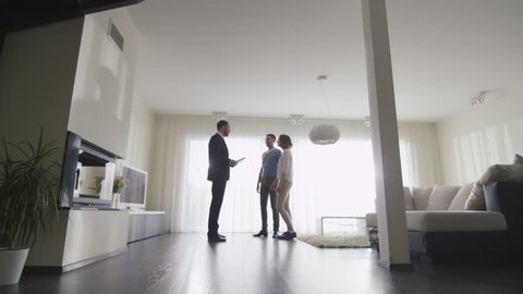 Real-estate Agent Shows New Apartments to Couple. Woman is Pregnant. Shot on RED Cinema Camera.