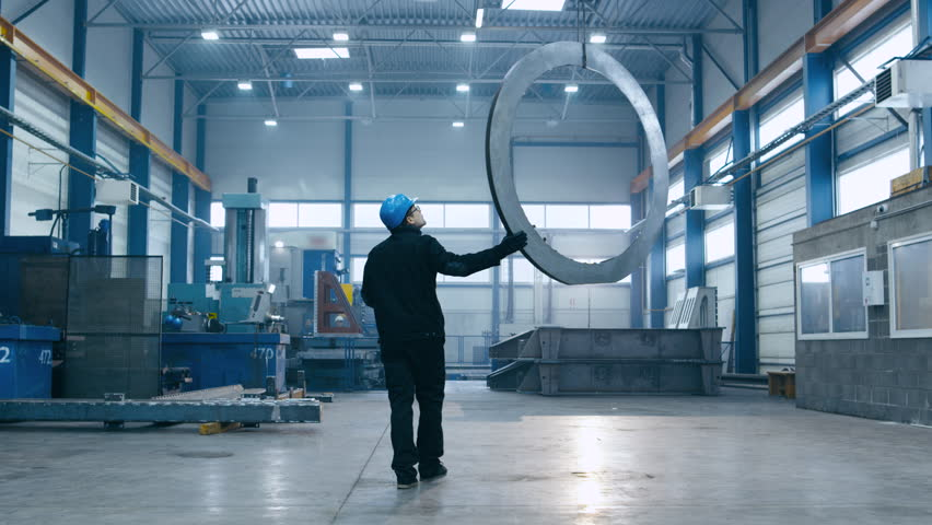 Factory worker in a hard hat is moving a metal detail with a remote crane. Shot on RED Cinema Camera.   Shutterstock HD Video #16958179