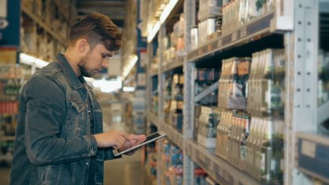 Manager With Tablet PC Checking Goods At Supermarket Warehouse