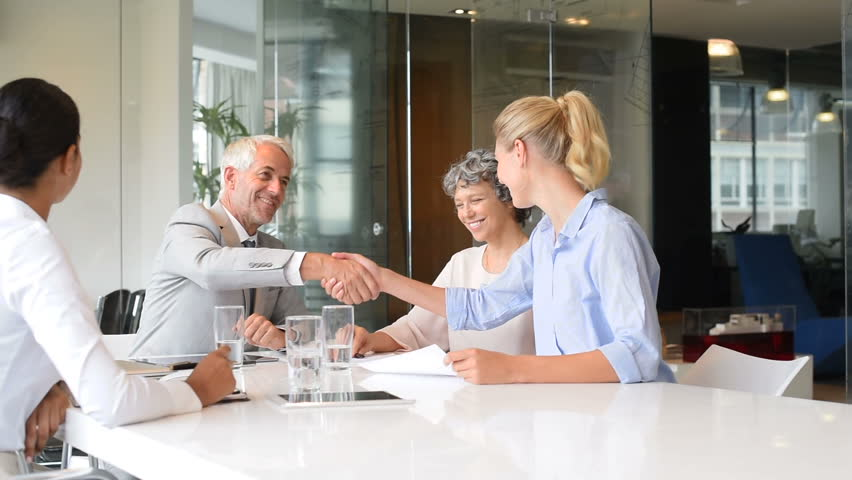 Business handshake to seal a deal after meeting between young businesswoman and senior manager. Senior businessman shaking hands to his assistance in a modern office in slow motion.