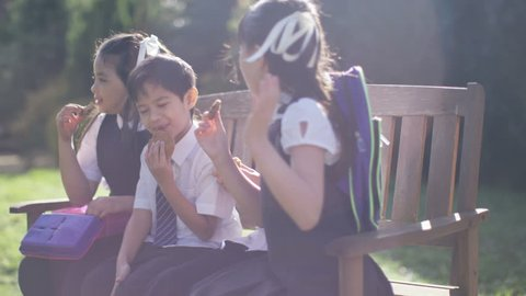 4K Happy young friends together, eating lunch on a bench in schoolyard UK - April, 2016