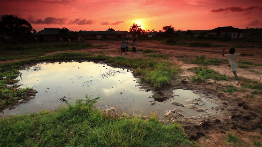 Group of boys play at village water hole at sunset in Africa