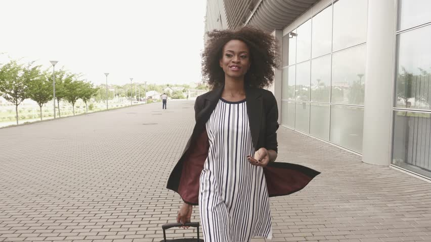 Full-length side view of slim african american business lady in short dress and high boots going to the airport with her luggage. Business trip concept