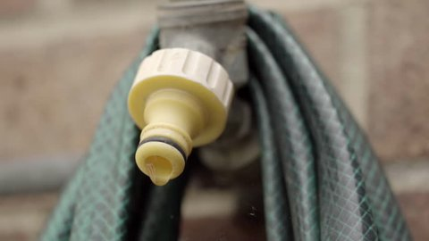 Outside water Faucet/Tap with dripping water HD stock footage. An exterior water tap with water dripping in slow motion and a green water hose