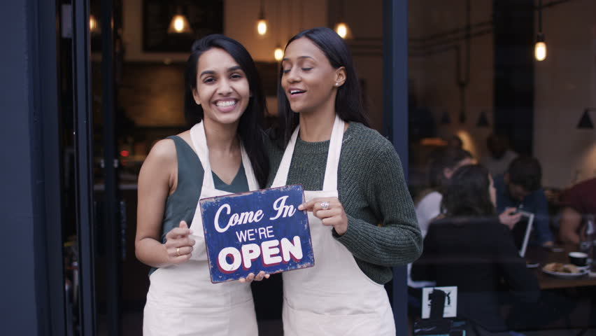 4K Happy women outside cafe hold up a sign to show they are open for business UK - April, 2016