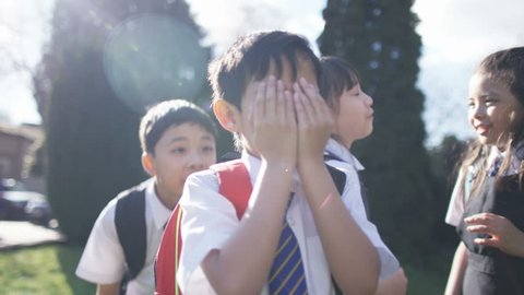 4K Happy young children playing outdoors in school playground UK - April, 2016