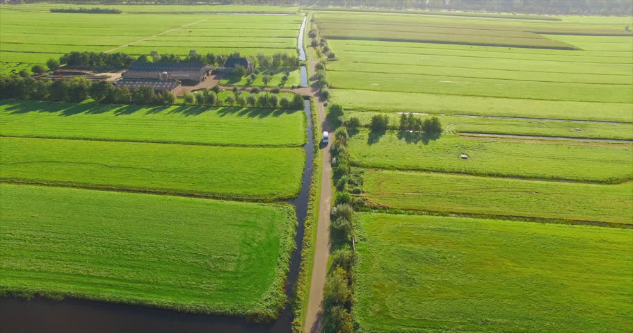 AERIAL: A white van drives towards a drone while it flies backwards on a small road through green fields in the Netherlands 4K / UHD / Ultra HD