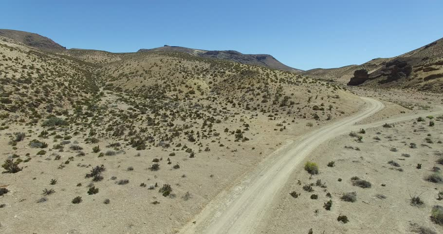 Aerial scene of dirt road in dry, desertic, mountainous landscape. Car, appears traveling,is lost behind a close hill. High perspective of dry panorama. Patagonia, argentina, Chubut, Piedra Parada.