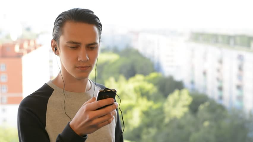 Attractive young man listening to music on headphones | Shutterstock HD Video #17086366