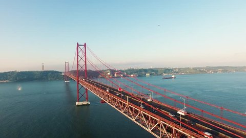 Cars on Bridge Ponte 25 de Abril over the Tagus river in Lisbon, Portugal at morning aerial view