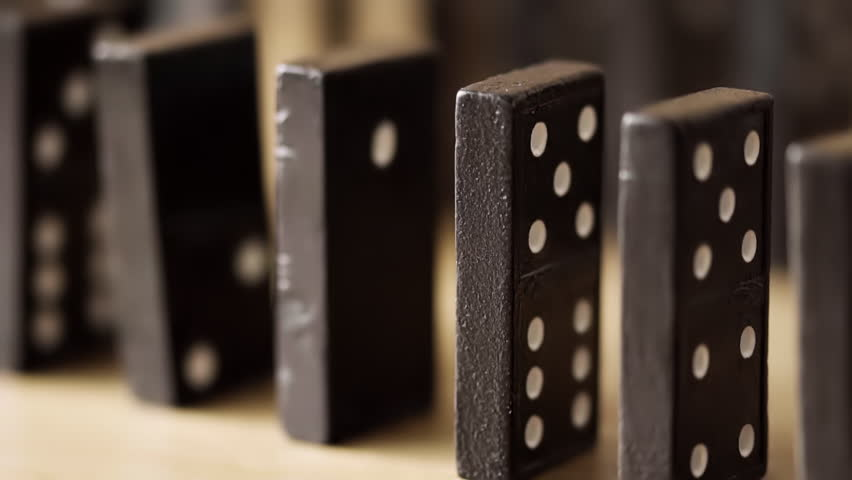 Dominoes falling against each other in slow motion in true macro close up.