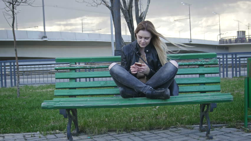 Cute happy girl with long blonde hair in leather jacket straightens hair with runny nose use gadget sitting on the bench in the wind 4k | Shutterstock HD Video #17113606