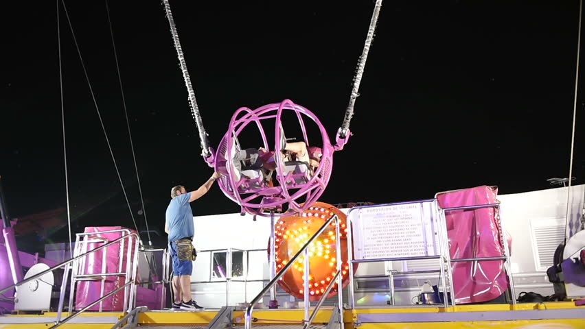STRASBOURG, FRANCE - CIRCA 2016: Couple last preparations for catapult ride at amusement park at night