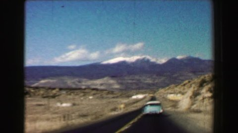 PALM SPRINGS, CALIFORNIA 1968: Open road trip travels following 50's classic car snow capped mountains western USA.