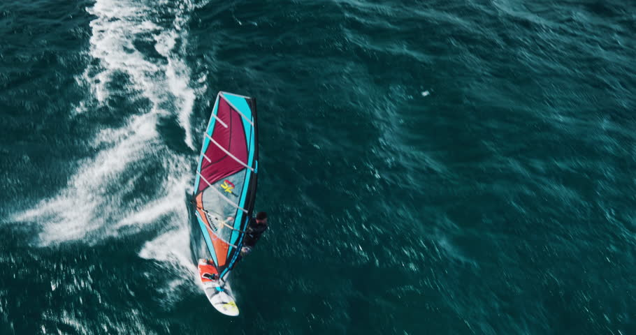 Aerial view of windsurfer gliding across blue ocean, extreme sport