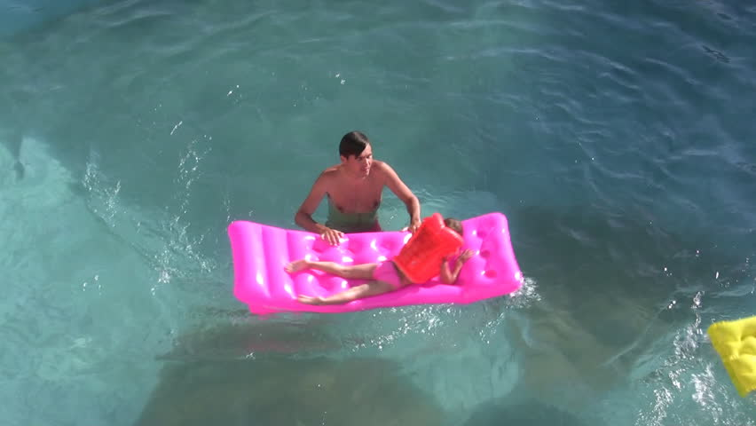 Father and child on mattress in pool